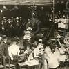 G1832 <br /> De uitvoering van de Kleppermarsch op 17 september 1913 op het feestterrein op de Overplaats van huize Rusthoff. Er deden zo'n 150 schoolkinderen aan mee en ze brachten zo een hommage aan de klepperman (klapwaker of nachtwacht), die een eeuw daarvoor nog 's nachts de wacht hield in het dorp en ieder uur zijn ronde deed. Op het podium de kinderen: links de jongens en rechts de meisjes. Links onder het baldakijn de muzikanten van het Chr. Fanfarekorps Crescendo naast hun vaandel. Foto: 1913.