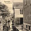 G0428 <br /> Een blik vanaf de Klapbrug over de Teylingersloot, het verlengde van de Sassenheimervaart; we kijken in noordwestelijke richting. Links de achterkant van het tolhuis aan de Teijlingerlaan en rechts de zijkant van het huis van H.A. de Leeuw. Verder naar achteren de bollenschuur van Blom. In deze ruimte heeft de Chr. Gereformeerde Kerk tijdelijk onderdak gevonden in afwachting van het kerkgebouw op de hoek Kerklaan/Bijweglaan. Foto 1920.