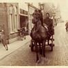 G0418 <br /> Kolenhandelaar T. Vos brengt met paard-en-wagen de kolen rond. De voerman was doorgaans Arie Vos (niet zichtbaar); naast hem zit een knecht. Zij zijn ter hoogte van de zaak van J. v.d. Meer, de klompen staan buiten. Verderop de wijnhandel van Van Niekerk. Foto: 1920.