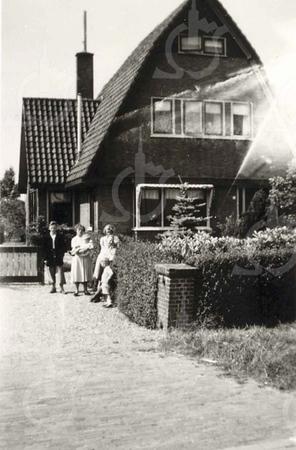 G0028 <br /> Rijksstraatweg 75, eertijds bewoond door de fam. Th. Verkleij, later bewoond door de fam. R. Broer. Voor het huis staat mevr. Verkleij met enige van haar kinderen. Het pand staat nu (2018) te koop. Foto: 1950.