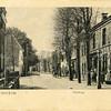 G0450 <br /> Hoofdstraat in zuidelijke richting. Links het huis van de fam. Jan Blom, gebouwd in 1892. Daarvoor woonde Cornelis Rhijnsburger in dit pand. Rechts de latere bakkerswinkel van Rhijnsburger. De man met de oliekar en hond is Gerrit Dannijs. Later werd hij fondsbode. Hij riep dan aan de deur: 'de fondsenbooi' of  'de ziekenfongst'. In de verte de Klapbrug. Foto: 1901.