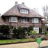 GM015  Hoofdstraat 161 en 163<br /> <br /> Dit dubbele, symmetrische woonhuis uit 1925 in art deco-stijl heeft een rietgedekte schilddak met steekkappen. Het ontwerp is van architect  Verhoog. Opgetrokken in rode baksteen, dat in halfsteens verband is gemetseld. Er zijn rollagen bij de plint en bij de onder- en bovendorpels aangebracht. Een betonnen latei is te zien boven de entree en eveneens boven de erboven gelegen loggia.<br /> <br /> Meer informatie is te vinden in 'Monumenten in Sassenheim', een uitgave van de Stichting Oud Sassenheim.