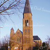 GM019  Hoofdstraat 186 - R.K. kerk St. Pancratius<br /> <br /> De oude kerk waarvan de eerste steen werd gelegd in 1869, was 40 el lang, 16 el breed en 17 el hoog. De toren was 40 el hoog en het geheel was in neo-gotische stijl ontworpen door H.J. van den Brink. De inwijding was in 1870.<br /> De nieuwe Sint Pancratius Kerk die vanaf 1912 in gedeeltes de oude kerk verving is ontworpen door architect Tonnaer. Het koor en het dwarsschip waren in 1929 klaar. Het geheel is in een late variant van de neo-gotische stijl opgetrokken. Er is rode baksteen gebruikt in kruisverband gemetseld en voorzien van gele bakstenen banden in twee lagen . Boven de diverse vensteropeningen zijn traceringen toegepast.<br /> <br /> Meer informatie is te vinden in 'Monumenten in Sassenheim', een uitgave van de Stichting Oud Sassenheim.