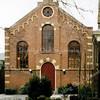 GM024  Hoofdstraat 137a  - voormalige gereformeerde kerk   <br /> <br /> Dit Gereformeerde kerkgebouw is gebouwd in 1876 door aannemer Guldemond in de toenmalige moderne stijl, de 'Waterstaatstijl', ter vervanging van de eerste afgescheiden Christelijk Gereformeerde Kerk, die in 1863 achter een woonhuis aan de Hoofdstraat was gevestigd. <br /> De kenmerken van de 'Waterstaatstijl' zijn te vinden aan de voorpui, zoals de afwerking van de bovenzijde met neo-romaanse boogjes en de gietijzeren  raamindeling.<br /> <br /> Meer informatie is te vinden in 'Monumenten in Sassenheim', een uitgave van de Stichting Oud Sassenheim.