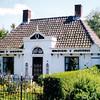 GM030  Hoofdstraat 100 <br /> <br /> Dit pand, gebouwd in 1839 bestaat uit één bouwlaag met een schilddak en is in de lengterichting aan de straatzijde gelegen. Dit duidde vroeger op rijkdom. De muren zijn in kruisverband gemetseld en wit gesausd. De middenrisaliet heeft een opvallende nadruk gekregen met een decoratief zwart/wit front en een piron als bekroning.<br /> <br /> Meer informatie is te vinden in 'Monumenten in Sassenheim', een uitgave van de Stichting Oud Sassenheim.
