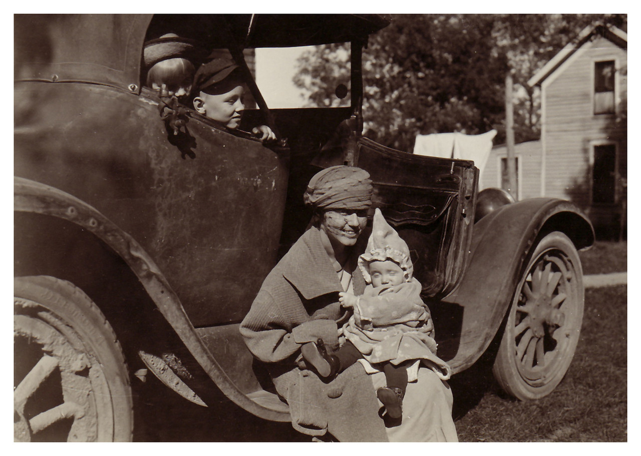 1921 Marianna and Morris Miller admiring new sister Eloise. Their mother, Geggy (Emma Whitmer Miller) sitting on running board of car.