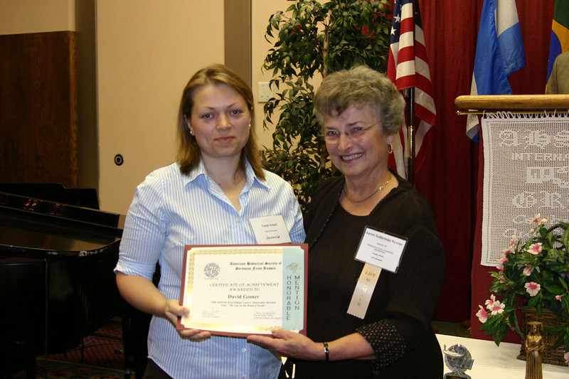 Tanja Schell (left) of Munich, Germany, accepted an Honorable Mention Award for Storytelling on behalf of David Gomer, who was unable to attend the convention.