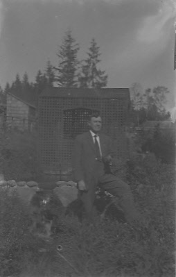 Edw C Dohm (KK) in front of springhouse, Seattle