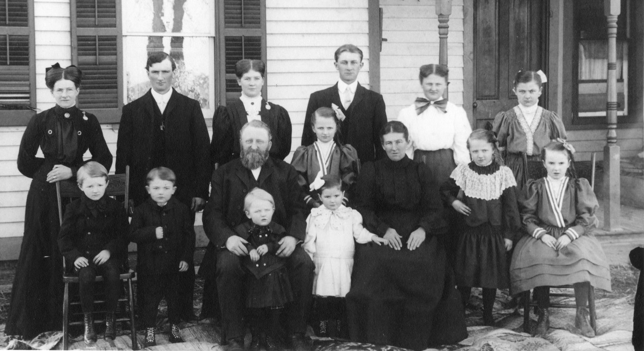 This is a portrait of Katherine Osterhaus Koopmann, my maternal grandmother's family, probably taken about 1908-09.  Other than my great-grandparents Henry and Charlotte Foerster Osterhaus, the only two we are certain about are the two on the far left: Kate Osterhaus Koopmann (dob January 3, 1880) and her brother Mathias (February 15, 1899).  Best guesses:   Back Row:  Kate, Henry (September 18, 1881), Elizabeth (October 17, 1886), Emma (May 7, 1894)(with bow in hair), Frank (September 15, 1884), Therese (February 15, 1889), & Anna (July 10, 1891). Front Row:  Matt, Joseph (May 6, 1901), Great Grandpa Henry (March 9, 1851), Al (January 7, 1907)in front, Martha (October 9, 1902), Great Grandma Charlotte (February 9, 1860), Agatha (April 14, 1897), & Clara (September 27, 1895).