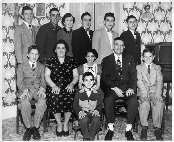 """""""The Hall Clan""""<br /> Top row (l to r): Lucien, Clifford (Pete), Ruth, Donald, Robert, my father Wilfred Jr. (Junior).<br /> Second row (l to r): Gerard, Memere Rose, Patricia, Pepere Wilfred, Richard (Nick).<br /> Front row: Roger (Butch)."""