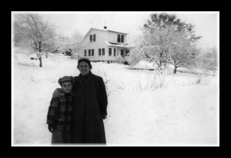 Roger (Butch) & Memere Rose (Couture) Hall posing in the snow with the across the street neighbors house in the backround.