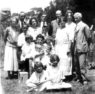 Seated in the chair Mary Elvira Wilkes Harrison (Mrs. Robert F.).  She's holding on the left chair arm Margaret Elizabeth Garey on the right arm Adelaide Bush Stevens.  In her lap Eleanor Ferrell and Neil Harrison Briggs.  Seated on the ground on the left Francis Harrsion Stevens on the right her older sister Lois Mary Stevens.  From left standing Elizabeth Sparkes (Harrison) Briggs, Stephen Thomas Garey, Stephen Thoms Garey, Jr., Elvira Azile (Harrison) Garey. Boy standing in front is Robert William Garey.  William Wilkes Harrison, Louis Ferrell (bald), Ruth Sigismunda (Harrison) Ferrell.  In front of them Permelia Adelaide (Harrison) Stevens and husband Frank Gilbert Haven Stevens.  Taken in Santa Monica, California about 1923.