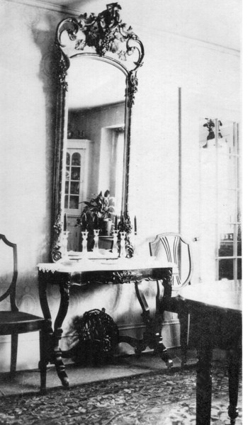 """Gilded mirror in Hill family. Passed by Gladys Hill Johnson to her son Robert Eugene Johnson. In great disrepair, disposed of after the latter's death in 1999.  Note on photo: """"End of Dining room. Dana [Hill] suggested to mother to thake the front of this mirror, paint the gold frame white, and put it in the bathroom."""""""