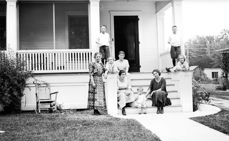 From L to R: Anneta Adelia Hull, one of two girl twins lying on either side of porch rails (Bernice & Bernadine), seated at top of stair is Bessie Mae, Lewis Allison is on the left and Harley Haas is on the right at the top of the porch rails.  The women on the front porch are probably Irving Leslie's sisters, L to R: Vera, baby Walter(?) and his mother Edna.