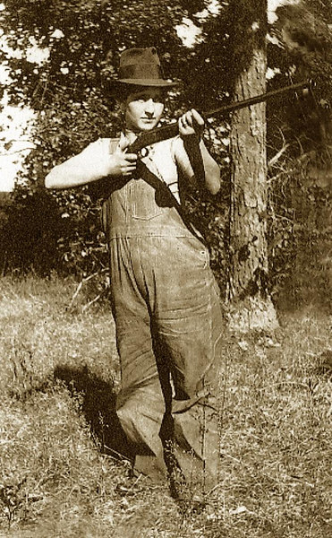 Having stuffed her dress into her husband Joe's Overalls, Maria (Fusi) Lombardi poses with her Stevens 12 guage, Model No. 85, <i>'Dreadnaught'</i>.  Milford, 1916.