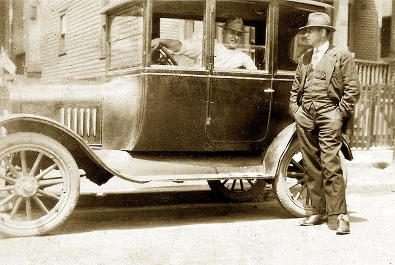 "The first car in the Lombardi family. Giuseppe (Joe) Lombardi in his 1922 Model T Ford on Fordyce St. Talking to family friend ""Rico"". Circa 1924. This Model T was a two door sedan that was purchased from Uncle 'Jack' Lombardi, which was years later sold in running condition to a junk yard for $5.00.<br /> <br /> ****Interesting Note: Rico taught Guy Lombardi Sr. how to play checkers.<br /> <br />  Also, it was with this car that Guy learned to drive, having received his first driver's license at age 14. In those days a driver's license was issued for life, and did not need to be renewed."