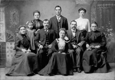 "LIEBE FAMILY: Family on left-  Rosalia and Jacob Breuchel and daughter Norma; Sophie Spann (back); Adolph Liebe (back); Amalia Liebe (seated in front); Bertha Liebe (back right); August and Emilia ""Minnie"" Spann."