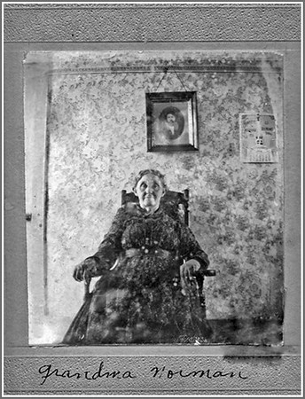 "MARTHA MERRITT NORMAN (1835-1901) This undated photograph shows Martha Merritt Norman seated in front of a photo of her husband, John Norman, who was likely deceased when this was taken.    Born in Indiana to George and Elizabeth (Scott) Merritt, her family moved to Iowa by the time she was a teenager. The 1850 census shows the family living at Fox in Davis County Iowa.  At about age 17, in February 1852, she married John Norman in Davis County.  Over the next 30 years, John and Martha 10 children, including Alatha (Norman) Durham, who would become mother of Leota (Durham) Maiden.  In addition to Fox County, the Normans also lived in Decatur and Page counties.  By 1870, their home was in Cherokee County.  John Norman died in 1882, and Martha reportedly married a widower named Thomas Phillips in 1877.  At the time of the 1900 census, Martha and Thomas lived in Aurelia, Iowa.  Martha died at Meriden, Iowa on 13 August 1901.  The cause was ""illness related to burns."" (Photo courtesy of Doug Henderson)"
