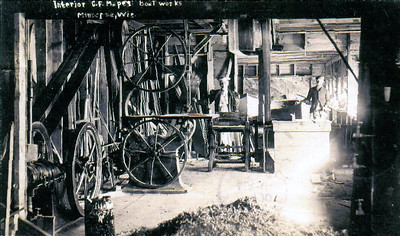 Interior of C.F. Mapes' Boatworks in Minocqua, WI. Calvin is in the background and his 4th wife, Lucy Ulman Mapes is on the left.