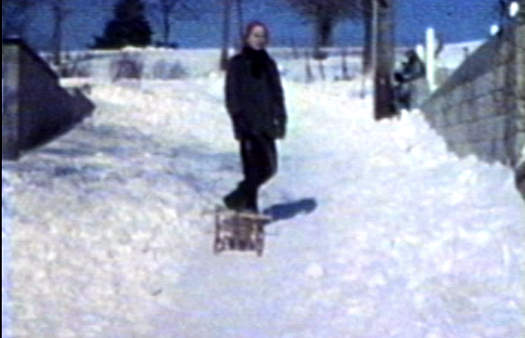 1962 SIoux City, IA Mark sledding in alley behind house at 3630 Jennings St.