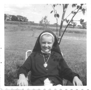 Dressed up in Aunt Alma's nun's habit...just for fun?  This photo was taken in the backyard of the house on Coxmill Rd, in Painswick. You can see the field our property backed onto, as well as the train tracks.