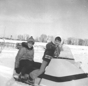 My sister and i on our Ski-Doo in the backyard of 241 Coxmill Rd house
