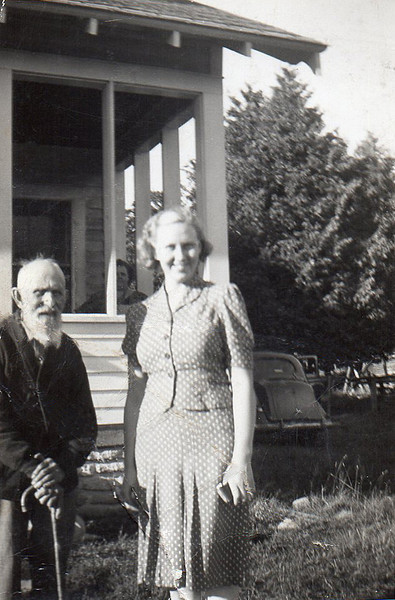 Irene and Grandpa Nikolaus Hammersmith by their house, Ella in the background