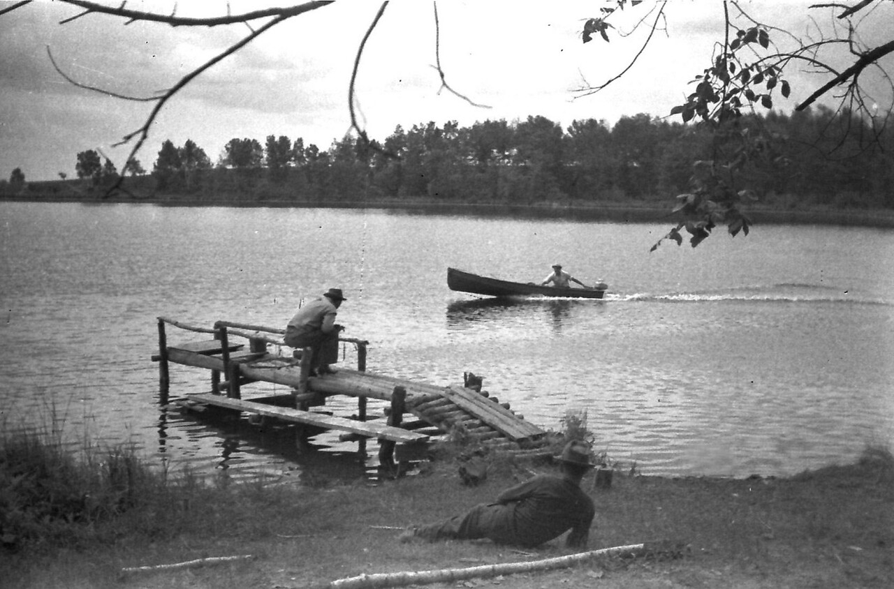 Burt in boat as friends look on. Tea Lake, Oscoda County. Fishing/Camping trip. ca. 1946.