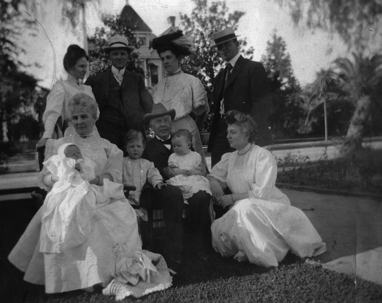 Dated 1906.  Row 1 Seated, Left to Right:  Sarah Katherine Pease Innes, holding Anne Katherine Innes (Phillips)?;  Walter Pease Innes, Jr.;  Daniel Innes holding Unknown child;  Unknown<br /> Row 2 Standing, Left to Right:  Margaret May Brown Innes;  Walter Pease Innes;  Unknown Woman - Sarah Innes Doran?;  Unknown Man - Willard J. Doran?  This looks like California - note the palm trees on the right - perhaps in front of the Innes home at 1331 Carroll Ave., Los Angeles