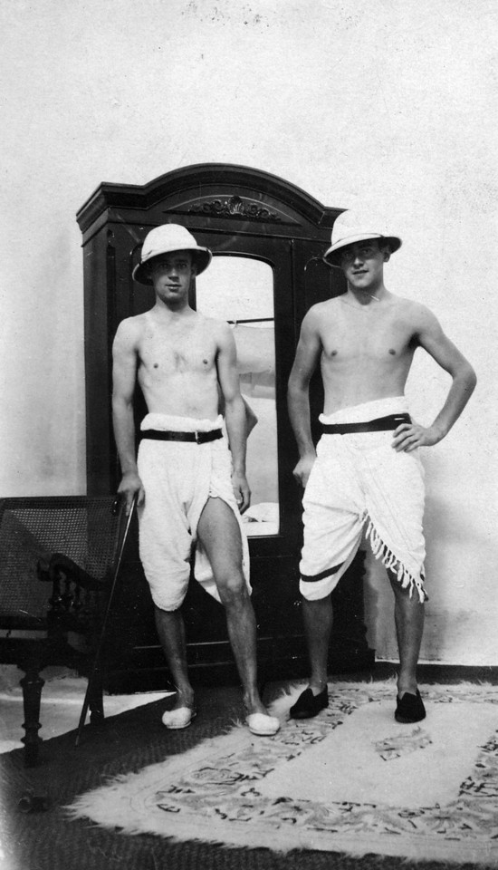 Handwritten on back:  Here is a picture of Bill and me taken in our hotel at Agra.  The hopees, sticks, belts and slippers are ours, the towels were the hotels'.  Many Indians dressed like this minus the first four articles mentioned.  Don't show this to Pekoe (?) or he will have a fit - use your discretion about burning it.  Love.
