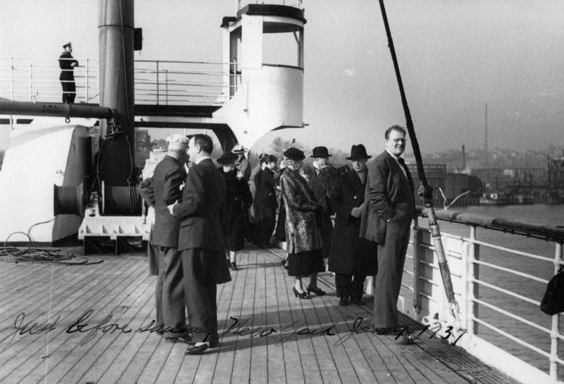 January 9, 1937.  Center, in fur coat:  Nora Phillips, and on ship's railing to right, Lee Eldas Phillips.  Handwritten on front of photo:  Just before sailing, New York Jan. 9, 1937.  Printed on back of photo:  Printed on board C.P.S.S. Empress of Britain by Associated Screen News, Limited, 5271 Western Avenue, Montreal