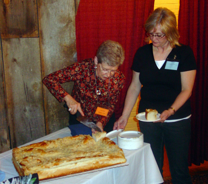 Vera Hoff of Rapid City, South Dakota does the cutting chores, while JoAnn Wangler of Bismarck, North Dakota helps serve the Kuchen.
