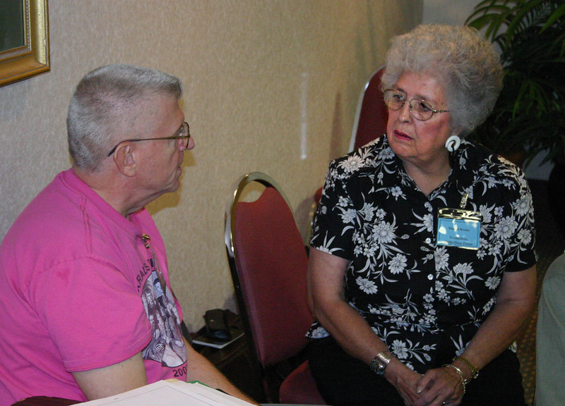 This is Muriel Kraus (at right) last September at a convention planning meeting in Casper.  She's visiting with Dick Kraus of Massachusetts -- believed to be a distant cousin of Muriel's husband, Bob.<br /> <br /> Her quilt design was inspired by photographs of iron crosses in Kansas cemeteries, taken by Laurin Leonhardt.  He has also made some small jewelry with these designs.  <br /> <br /> According to Muriel, Laurin designed all of the iron crosses used for the quilt on his computer, using his own photographs and some that he found on the internet.  They've been modified somewhat to be able to adapt them for fabric.  The patterns have been shared with many people, including Jeanne Rupp of Hays, Kansas, whose tea towels will also be raffled in Casper.