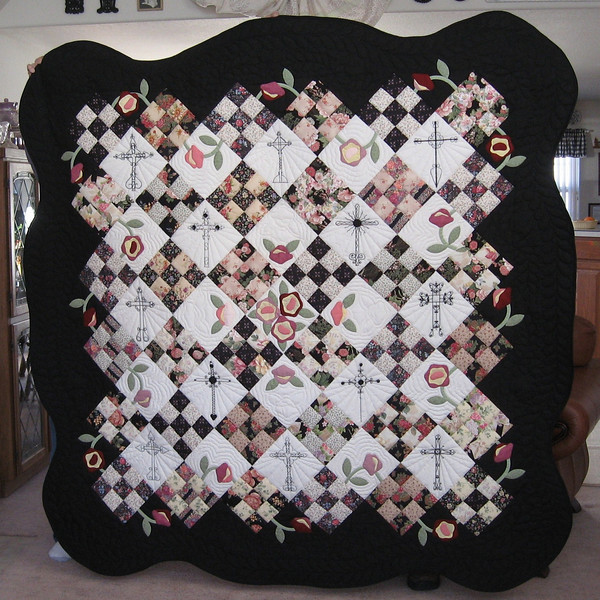 "The pattern for the quilt came from a book <i>Pink Lemonade</i> by Linda Johnson and was named ""Day and Night"" in the book.    Muriel says, ""It was appropriate because it had 12 plain blocks in it that we could use to embroidery the iron crosses on.  This, of course, is the main attraction of the quilt.   You may click on the photograph to see a larger image.  Alma (Sauer) Woodard, Kathy Rein, and I embroidered the crosses.  It has applique roses in the center, also a vine running about the outer edge with roses.  It has 36 nine-patch blocks in assorted light floral prints of pink, red and peach.  The blocks are set on point.  It is approximately 78"" square, with a scalloped edge.  It has been beautifully machine quilted by Floy at the ""Back Door Quilter"" in Lander.  In addition to inspiration from Evelyn Lovell, Muriel acknowledged help from Laurin and Cindy Leonhardt, Janet Bath, Alma Woodard and Kathy Rein.  <a href=""http://www.germansfromrussia-casper.blogspot.com"">Return to G-R Blog</a> or continue in this gallery."