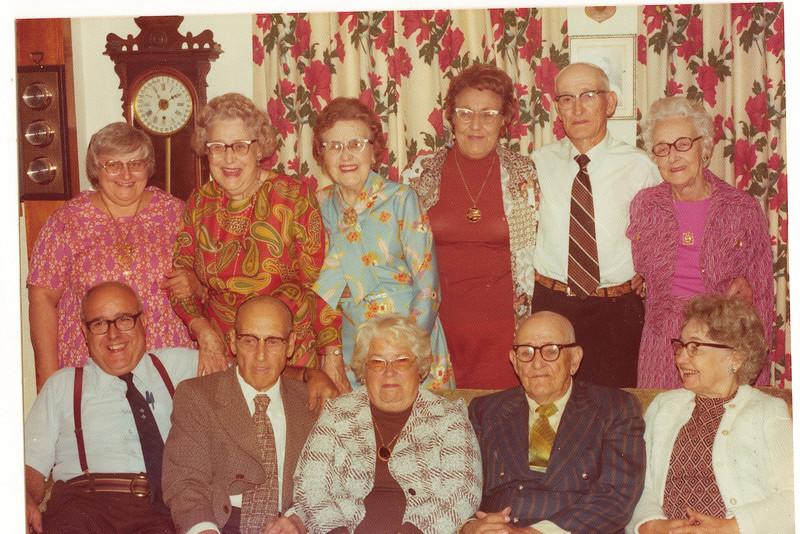 "Front row left to right: Alvin Glen Dew (1920 - ), Burl Orville Dew (1904-2001), Vada Mae (Yarbrough) Dew (1905-1993), Perry Winfield Dew (1891-1975), Dorothy (Data) Dew.  Back row left to right: Viola ""Vickie"" Clara (Radke) Dew, Mary Lavinna Dew (1895-1992), Josie Louisa Dew (1897-1999), Alice Martha Dew (1902-1999), Byron Elmer Dew (1893-1986), Glenna Ellen Dew (1900-1997)   Written in the Rogers Reunion Photo Album Volume III page 21 to the upper right of the photo ""Back: Vickie (Mrs Ed Dew), Mary, Josie, Alice, Elmer & Glenna. Front: Glen Dew, Burl, Vada (Mrs Burl Dew), Perry & Dorothy (Mrs. Perry Dew)"
