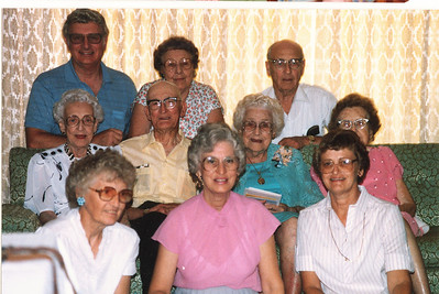 "Front row: Donna Rogers Dew (1927-2006  ), Edna Ruth Dew (1925-2003), Evelyn Lois Dew (1929-2004) Middle row: Glenna Ellen Dew (1900-1997), Byron Elmer Dew (1893-1986), Mary Lavinna Dew (1895-1992), Josie Louisa Dew (1897-1999) Back row: Robert Edwin ""Ed"" Dew (1924-2006), Alice Martha Dew (1902-1999), Burl Orville Dew (1904-2001)  Written in the Rogers Reunion Photo Album Volume III page 22 ""11 Aug 1985 Mary's 90th birthday. Left: Ed, Alice, Burl. Next row: Glenna, Elmer, Mary, Josie, Next row: Donna, Edna, Evelyn.  Birthday party for Mary's 90th at Margaret Yount's home."""