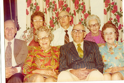 "Front row left to right: Burl Orville Dew (1904-2001), Mary Lavinna Dew (1895-1992), Perry Winfield Dew (1891-1975), Josie Louisa Dew (1897-1999)  Second Row left to right: Alice Martha Dew (1902-1999), Byron Elmer Dew (1893-1986), Glenna Ellen Dew (1900-1997)   These are the children of William Alfred Dew (1869-1965) and his first wife Fannie Belle Hays (1871-1919) Written in the Rogers Reunion Photo Album Volume III page 21 above the photo ""Sep 28, 1975 – Alice, Elmer, Glenna, Burl, Mary, Perry & Josie."""