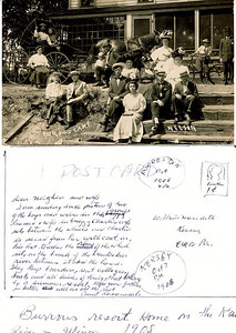 """Burrows resort home on the Kaukakee River, Illinois 1908"" On the back of the postcard in the Rogers Reunion Photo Album Volume II. Is the following: addressed to William Meredith, Kersey, Elk Co, Penna, and postmarked Kersey Oct 7 pm 1908 and Forreston Oct 8 1908 4 pm,  Dear Neighbor and Wife,  I am sending the picture of two of the boys and wives in this group, Leonard & wife in buggy, Charlie's wife sits between the wheels and Charlie is second from her with coat on - his hat touches the rim of the wheel. Sits on the banks of the Kamkakee river between it and the house – They keep boarders, rent cottage, boats and all kinds of things that belong to a summer resort.  Hope you father is better as well as all the rest.  Signed Aunt Rosannah"""