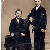 Seated: Chester William Rowland (June 26, 1872 - May 8, 1949) son of Rosannah Merilla Rogers and her second husband Elias Rowland. <br /> Standing: William Alfred Dew (March 29, 1869 - June 12, 1965) son of Edwin Dew and Percilla Adeline Rogers. The boys' mothers were sisters. This is a tin type.<br /> Rogers Reunion Photo album Volume 1, page 27.