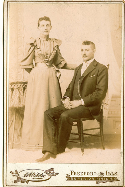 """Flora Permilla Frantz (August 9, 1867 - 1961) daughter of Lavinna Adelaide Rogers and James A. Frantz and her husband Charles Melvin Conrad (September 5, 1872 - April 12, 1935) son of Sam Conrad and Elizabeth Garman..  They married on August 3, 1893.  The Photograph has stamped on it """"G.A.Webster   Freeport, Ills""""  Written in the Rogers Reunion Photograph Album Volume 1, page 24 """"Charles & Flora (Frantz) Conrad wedding photo: married May 21, 1864 and moved to Ogle Co Il in the fall.  They first moved in the fall to Joseph's farm in Carroll County then to Ogle Co in 1865 when Joseph brought his family to Illinois""""  This notation mistakenly refers to Livinna Adelaide Rogers who married James A. Frantz on May 21, 1864.  Lavinna was Flora's mother."""