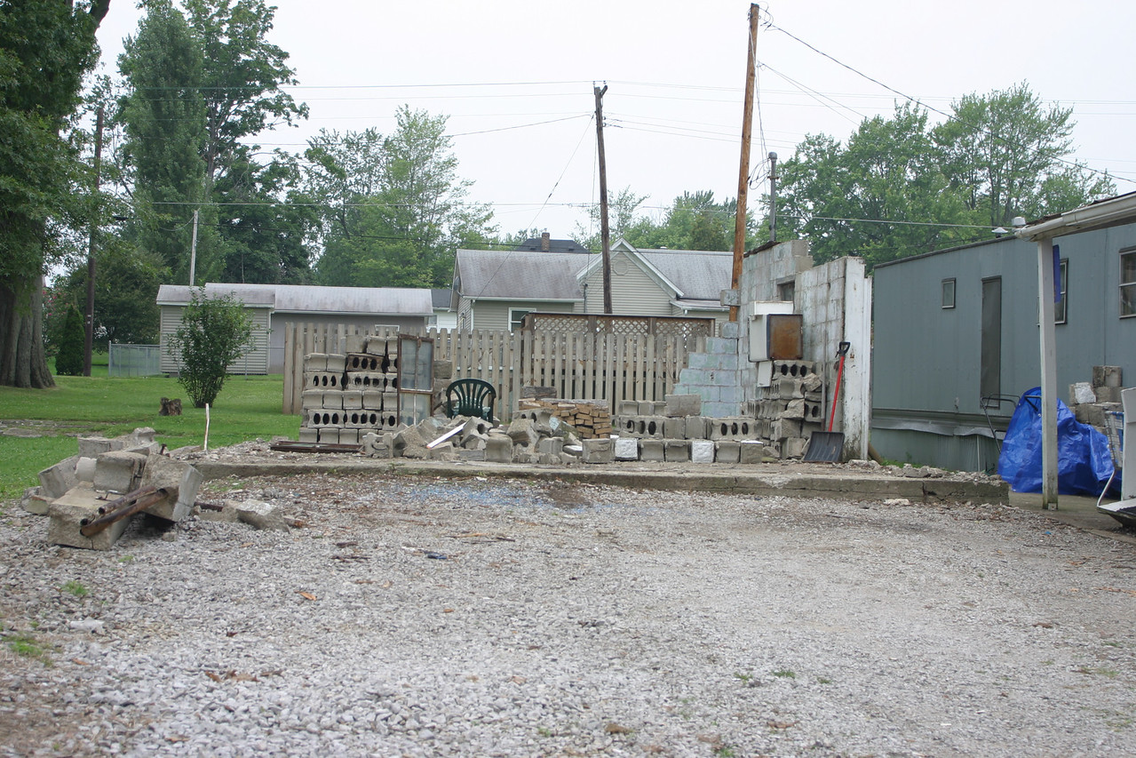 This was the Sanders house at the SW corner of Sherman and Center Streets in Brazil, Indiana.   The concrete pad and blocks are all that remain.  Photographed July 31, 2004.  In the background is the 422 Center Street house.
