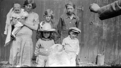 Mary Louisa in cowboy hat. Lady holding the baby may be Sarah Estes Wolfe holding her son Raymond Dale. Others are unknown. Sarah was married to Clarence Ellsworth Wolfe a farm hand of Oscar's. circa 1928/9.