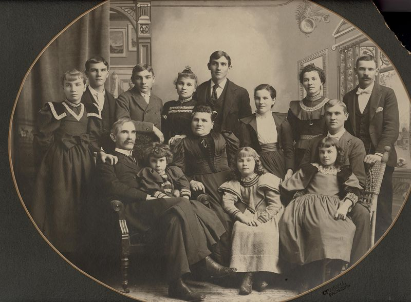 "Written on the back in Hazel Benshoff's hand<br /> "" Wesley Stevens and His Family. He was grandpa Stevens youngest brother.  They lived at about 595 No. Marengo Ave Pasadena then moved to Long Beach, Calif.<br /> 7 girls Lou standing back of Aunt Jennie, Winnie, Claudine (named after mama) Viola, Beatrice, Ina, Myrtle <br /> 5 boys Mitchel (at right), Chester, Dyson, Spencer 1 boy I can't remember his name.""  The children are: Lucretia ""Lou"" May Stevens, Raymond B. Stevens, Spencer Roy Stevens, Winifred ""Winnie"" Ethel Stevens, Chester W. Stevens, Dyson F. Stevens, Wesley Mitchell Stevens, Ina B. (Stevens) McSwain, Myrtle ""Mertie"" Sarah (Stevens) Brakesman, Claudine E. Stevens, Beatrice Stevens, Viola (Stevens) McBride."