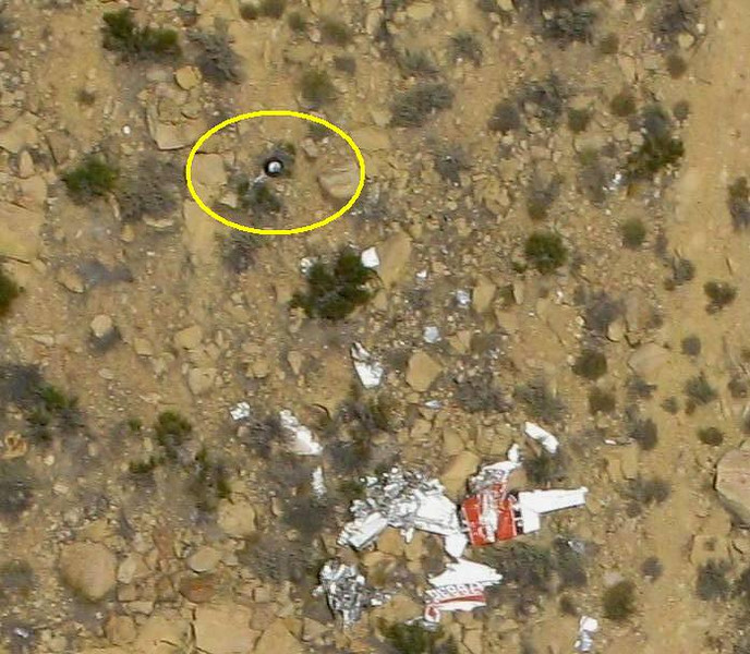 Visible on the steep slope and not far from the main body of wreckage is a separated main landing gear with wheel and tire.