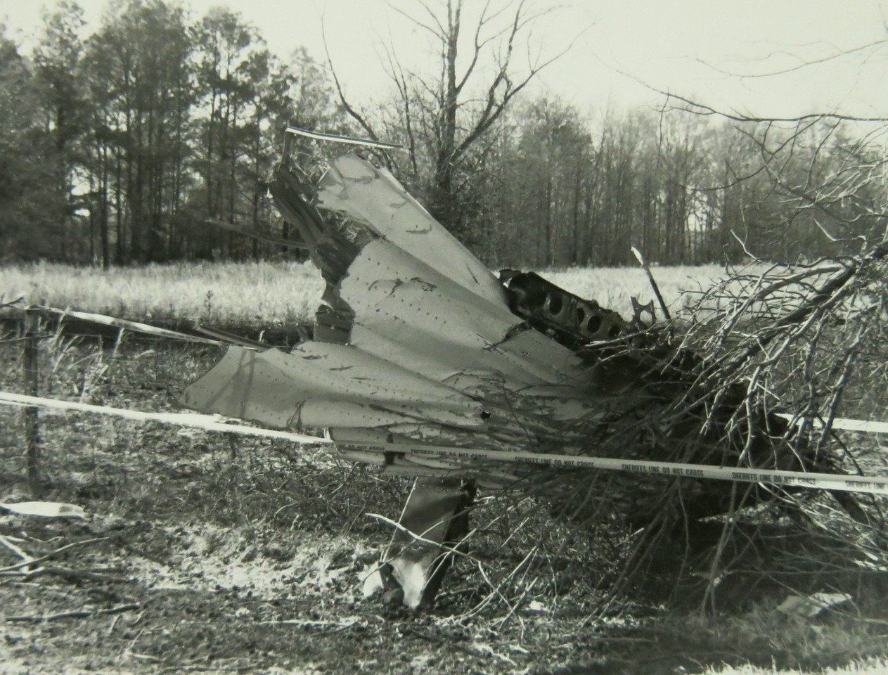Even though the DC-3's right wing struck the telephone pole as it crossed into the pasture, it remained relatively intact. However, the outer left wing was torn off as it passed through the tree line.<br /> <br /> This photo shows a fragment of the outer left wing leaning on the farmer's boundary fence bordering his property.