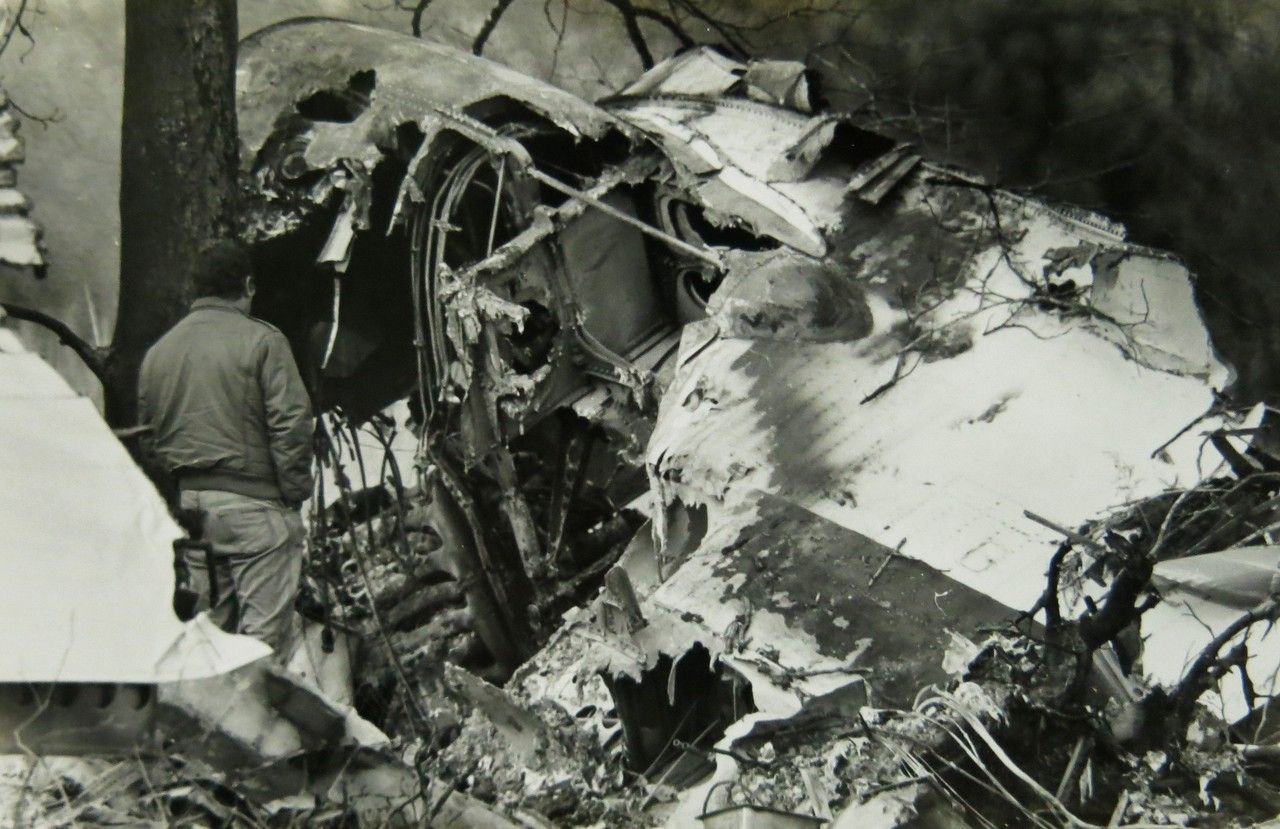 An NTSB investigator inspects the DC-3's wing root attepting to trace the source and path of the inflight fire.<br /> <br /> As with most accidents involving severe fire damage, much of the initial cause evidence is destroyed, while some evidence such as soot patterns is created by the fire.