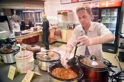 Matt Hamilton/Daily Citizen-News Democratic party chair Adam Griffin spoons out small amounts of chili for the judges on Saturday during the Democratic Party chili cookoff at the Community Center.