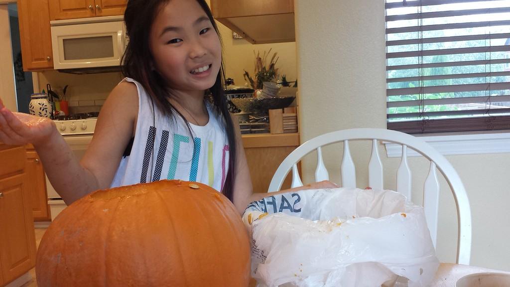 10.31.15 isabella carving her pumpkin