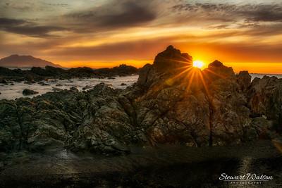 Sun flare between the rocks at sunrise