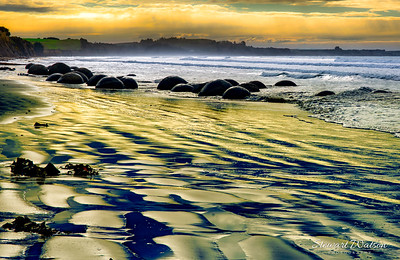 vibrant sky colour reflected on the beach at low tide at the famous and iconic Moeraki Boulders at Sunset